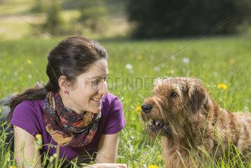portrait von junger Frau mit irischem Terrier auf Blumenwiese