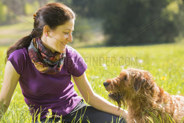 portrait of a young woman and Irish terrier in meadow