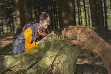 junge frau spielt mit irischem Terrier im Wald