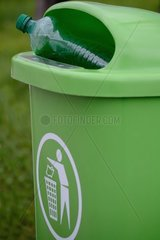 gruener Abfallkuebel mit gruener PET-Flasche