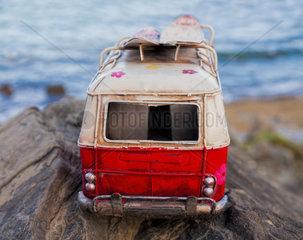 model car of a classic hippy van on a rock on the coast