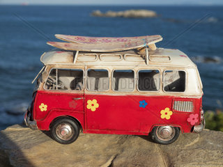 model car of a volkswagen T1 classic hippy van on a rock on the coast