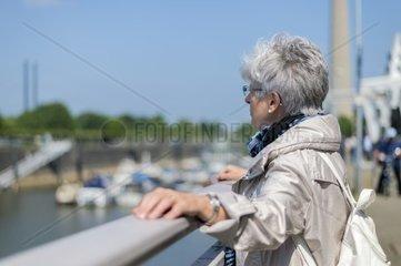 Eine Seniorin steht am Gelaender und schaut auf den Duesseldorfer Stadthafen