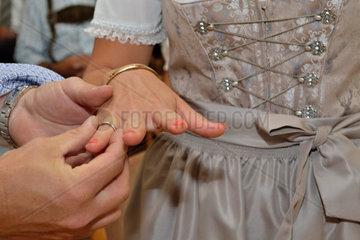 Braeutigam steckt Braut in Tracht den Ehering an