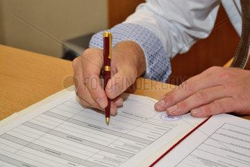 Mann in Tracht unterschreibt Urkunde
