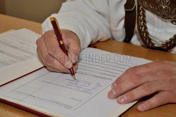 modisch gekleideter Mann unterschreibt Urkunde