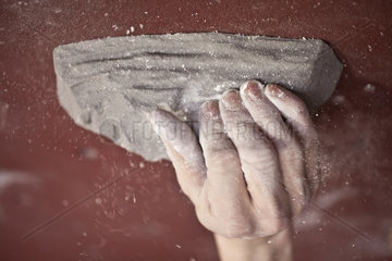 Climbers hand on a grip in a climbing hall  with chalk dust and red backround