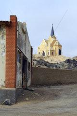 Felsenkirche ueber verfallenen Gebaeuden in Luederitz  Namibia  Afrika