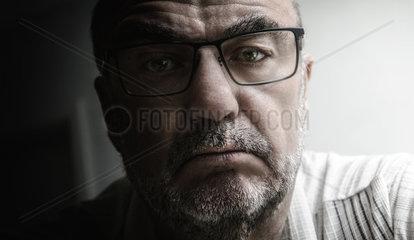 Portrait eines aelteren Mannes im Seitenlicht eines Fensters mit Kamerablick