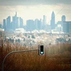 Frankfurt am Main Skylne Ansicht von Westen mit gruener Ampel im Vordergrund