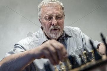 ein Mann am Schachbrett beim Setzen der Schachfiguren