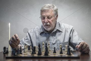ein Senior sitzt an einem Tisch und betrachtet die Situation auf einem Schachbrett