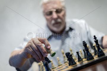 ein Senior fuehrt einen Schachzug aus
