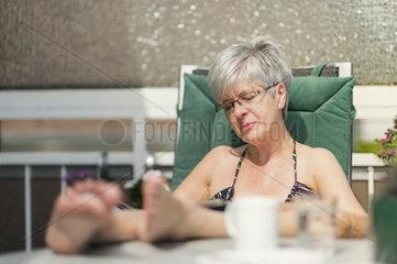 eine Seniorin sitzt lesend auf dem Balkon und geniesst den Sonnenschein