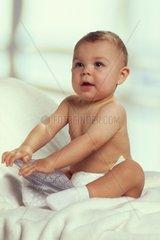 Ein Baby sitzt nur mit einer Windel bekleidet auf einem Bett