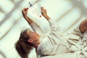 Eine Frau hat eine Waermflasche mit der Aufschrift So richtig nett ist es nur im Bett in der Hand