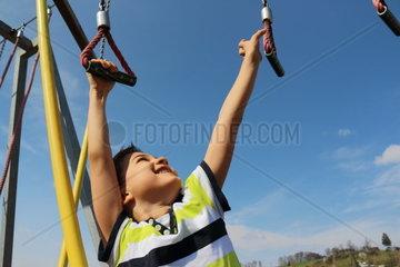 Glueckliches Kind klettert von Seil zu Seil
