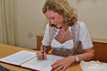 Braut unterschreibt in Tracht am Standesamt Heiratsurkunde
