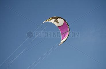 Drachen zum Kitesurfen vor blauem Himmel  im Wind