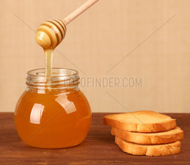 Pot of honey  rusks and wooden dipper on table