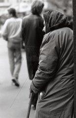 Alte Frau mit abgetragenen Mantel und Wurstzipfel in der Tasche