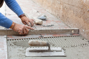 worker leveling new pavement with a specific tool