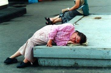 Obdachlose Frau liegt auf einem Podest