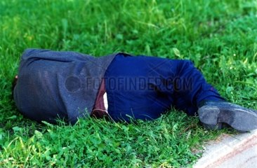 Obdachlose Person liegt im Rasen