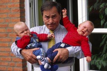 Vater mit Zwillingen auf dem Arm