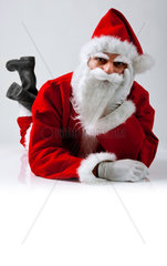 Santa Claus lying down with serious expression