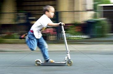 Junge faehrt Roller auf Gehsteig