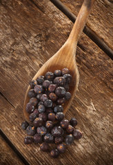 Handful of Juniper berries isolated on wooden table