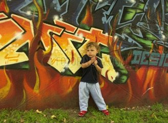 little boy standing in front of graffiti wall