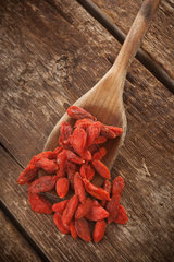 Dried goji berries isolated on wooden table