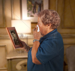 Old lady crying watching a photo of a deceased person