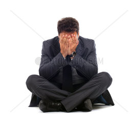 Depressed young businessman sitting on the ground over white
