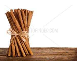 Bunch of Ceylon cinnamon on wooden table over white
