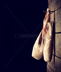 Old used pink ballet shoes hanging on wooden background