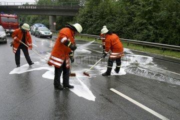 Feuerwehrmaenner reinigen die Unfallstelle