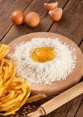 Italian pasta tagliatelle homemade on wooden table