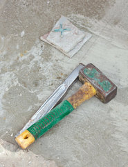Awl and big hammer on concrete flooring