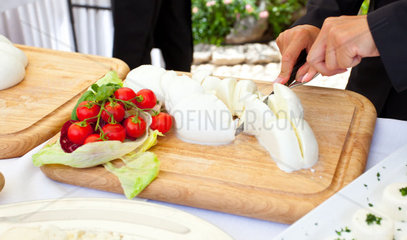 Sliced of mozzarella from the waiter during a wedding reception