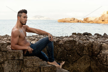 Young handsome muscular man on the stony beach