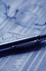 Brille  Stift und Wirtschaftsteil einer Zeitung