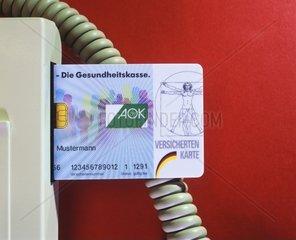 Eine Krankenversicherungskarte der AOK steckt in einem Lesegeraet