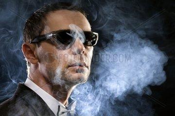 Mann mit Sonnenbrille im Rauch