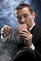 Mann mit Zigarette beim Kartenspiel