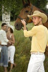 Mann mit Pferd und Paar im Hintergrund