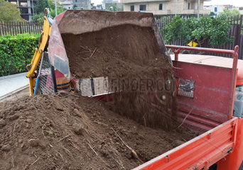 Excavator loading ground in truck tipper in the garden