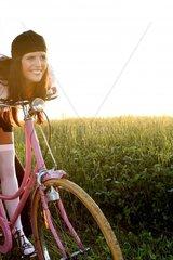 Junge Frau mit rosa Fahrrad im Freien